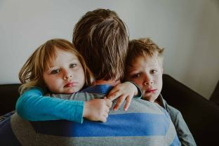 Picture of children sadly hugging their father